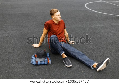 Young handsome man in a stylish red T-shirt with a cap in trendy jeans in trendy sneakers resting sitting on the basketball court on a warm summer day. Attractive guy relaxes after the game. #1335189437