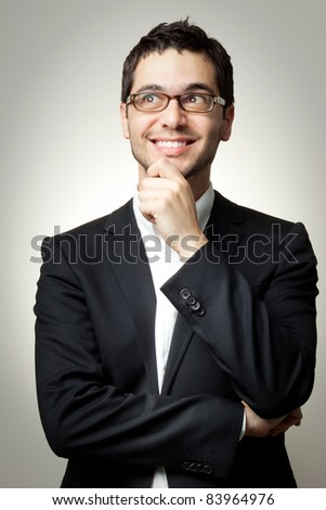 Young handsome man in black suit and glasses looking at copy-space smiling, thinking or dreaming