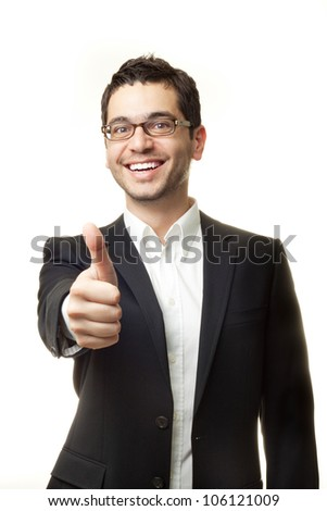 Young handsome man in black suit and glasses smiling and showing thumbs up isolated on white background