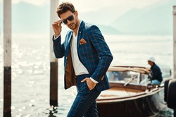Young handsome man in classic suit wear sunglasses over the blurred lake