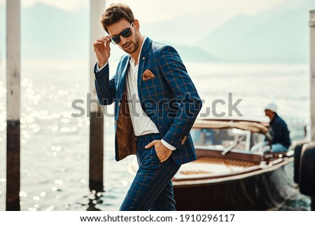Young handsome man in classic suit wear sunglasses over the blurred lake  Foto stock ©