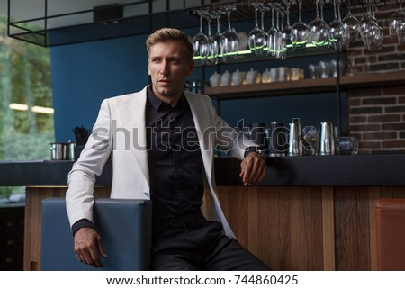 Young handsome man in classy suit sitting at counter in bar looking away confidently.  #744860425