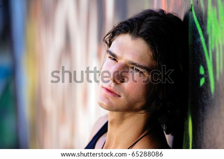 young handsome man in front of graffitti wall