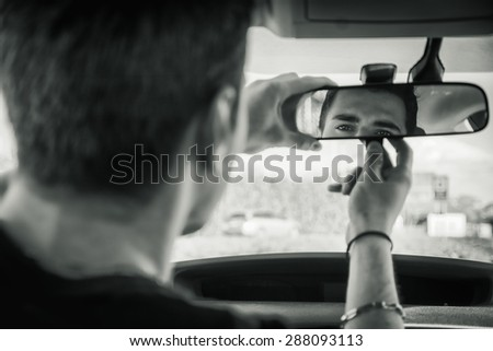 Young handsome man in his car adjusting rear view mirror during day #288093113