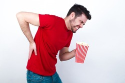 Young handsome man in red T-shirt against white background eating popcorn Suffering of backache, touching back with hand, muscular pain