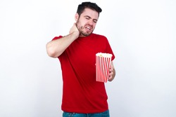 Young handsome man in red T-shirt against white background eating popcorn Suffering of neck ache injury, touching neck with hand, muscular pain