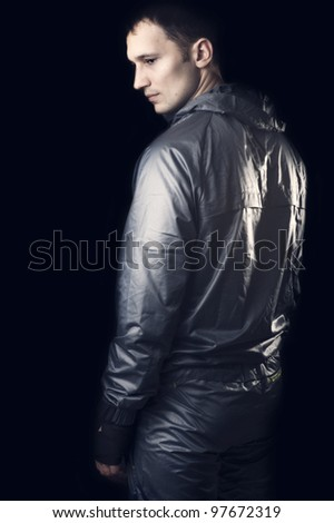 Young handsome man in sportswear on black background