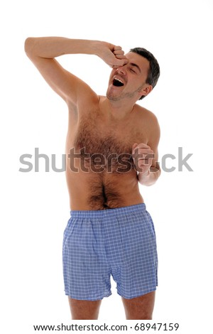 Young handsome man in underware waking up in the morning and yawning. isolated on white background