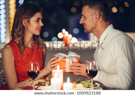 Young handsome man in white shirt giving present to his girlfriend while have romantic dinner at home
