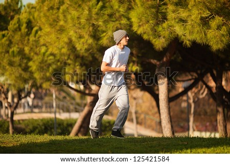 young handsome man jogging in public park