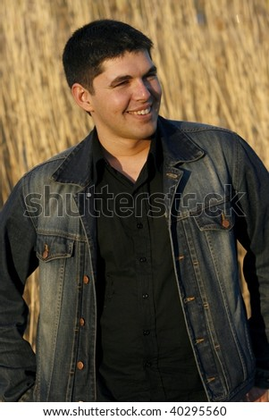 Young handsome man laughing, reed on the background