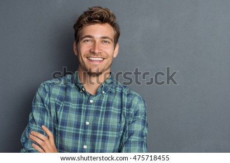 Young handsome man leaning against grey wall with arms crossed. Cheerful man laughing and looking at camera with a big grin. Portrait of a happy young man standing over grey background. #475718455