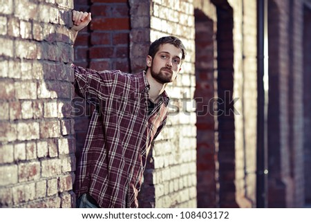 Young handsome man leaning against the brick wall and looking for someone, he is wearing checked shirt and jeans