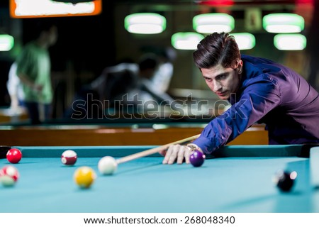 Young handsome man leaning over the table while playing snooker