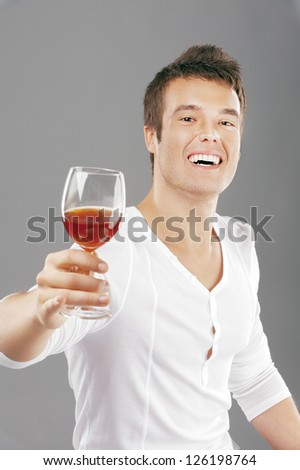 Young handsome man lifts toast about wine glass, on gray background.