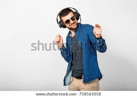 young handsome man listening to music in headphones, white studio background, isolated, smiling, happy stock photo