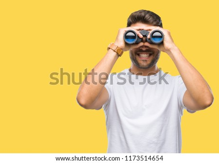Young handsome man looking through binoculars over isolated background with a happy face standing and smiling with a confident smile showing teeth