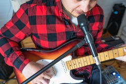 Young handsome man, musician, singer studying,practicing to play electric guitar at home,singing songs into microphone.Hobby,passion.Guy in red plaid shirt sits on chair.DJ console,speakers,equipment.