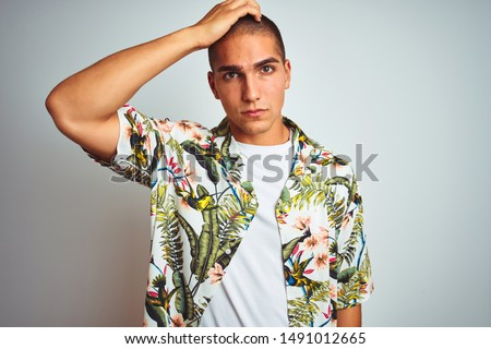 Young handsome man on holidays wearing Hawaiian shirt over white background confuse and wonder about question. Uncertain with doubt, thinking with hand on head. Pensive concept.