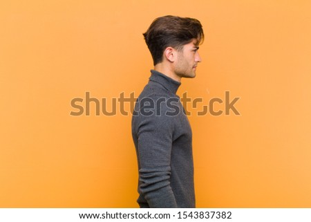 young handsome man on profile view looking to copy space ahead, thinking, imagining or daydreaming against orange background