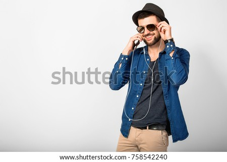 young handsome man on white studio background, isolated, listening to music on earphones, holding phone, smiling, happy stock photo