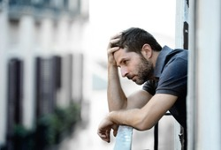 young handsome man outside at house balcony alone looking depressed, destroyed, sad and suffering emotional crisis and grief in life problem concept on an urban background