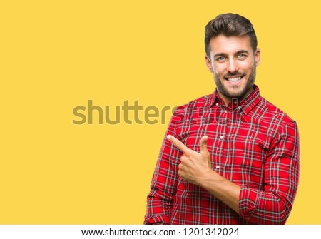 Young handsome man over isolated background cheerful with a smile of face pointing with hand and finger up to the side with happy and natural expression on face looking at the camera.