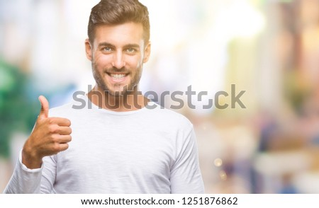 Young handsome man over isolated background doing happy thumbs up gesture with hand. Approving expression looking at the camera with showing success. #1251876862