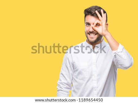 Young handsome man over isolated background doing ok gesture with hand smiling, eye looking through fingers with happy face. #1189654450
