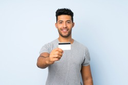 Young handsome man over isolated background holding a credit card