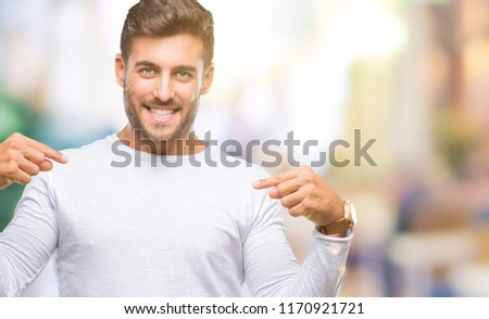Young handsome man over isolated background looking confident with smile on face, pointing oneself with fingers proud and happy. #1170921721