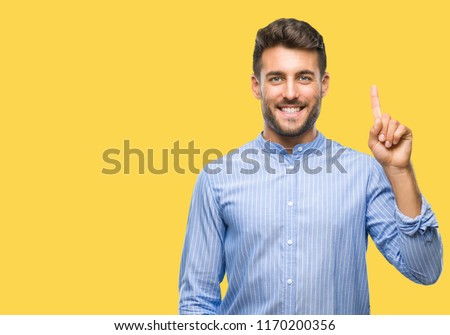 Young handsome man over isolated background showing and pointing up with finger number one while smiling confident and happy.