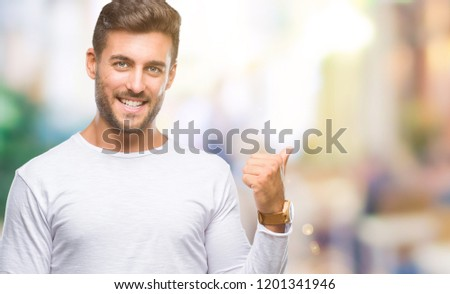 Young handsome man over isolated background smiling with happy face looking and pointing to the side with thumb up. #1201341946