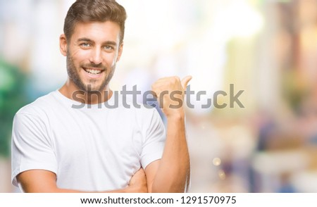 Young handsome man over isolated background smiling with happy face looking and pointing to the side with thumb up. #1291570975