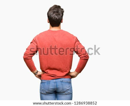 Young handsome man over isolated background standing backwards looking away with arms on body