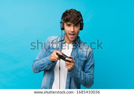 Young handsome man over isolated blue background playing at videogames