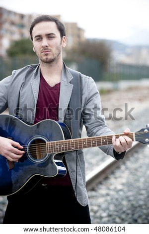Young handsome man playing guitar in urban background