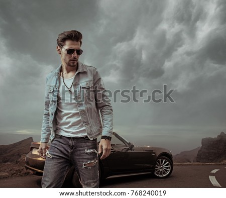 Young handsome man posing in a convertible car