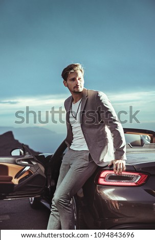 Young handsome man posing next to a convertible car