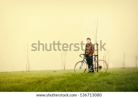 Young handsome man posing on the green meadow with vintage bike
