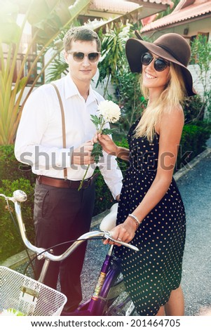 Young handsome man present flower to his girlfriend at first date. Posing outdoor in city garden with retro bike, wearing stylish vintage outfit and sunglasses.