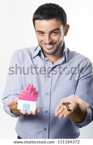 Young Handsome Man presenting Miniature House and Key #151184372