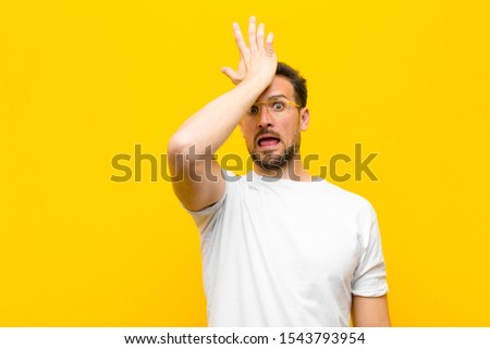 young handsome man raising palm to forehead thinking oops, after making a stupid mistake or remembering, feeling dumb against orange wall