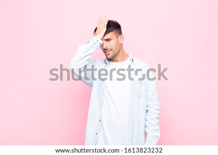 young handsome man raising palm to forehead thinking oops, after making a stupid mistake or remembering, feeling dumb against pink wall