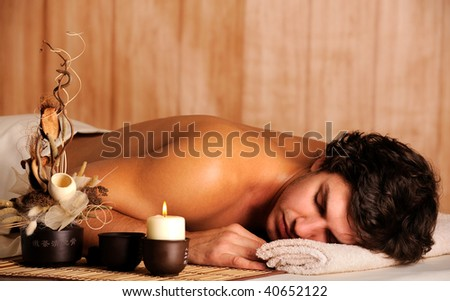 Young handsome man relaxing in spa salon - high angle view