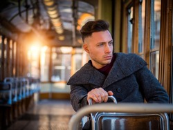Young handsome man riding on empty tram or old bus in city, wearing winter clothes, sitting