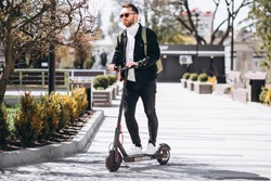 Young handsome man riding on scooter in the park
