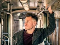 Young handsome man riding on tram or old bus in city, wearing winter clothes