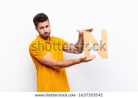 young handsome man sad, depressed, unhappy, holding the letter N of the alphabet to form a word or a sentence. Foto stock ©