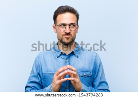 young handsome man scheming and conspiring, thinking devious tricks and cheats, cunning and betraying Foto stock ©